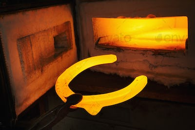 A red glowing horseshoe shape, held with tongs, and an open furnace. Glowing heated metal.