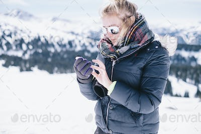 A woman on the ski slopes looking at her smart phone.