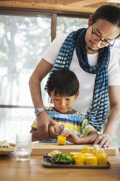 Man and boy standing at a table, preparing corn on the cob, smiling.