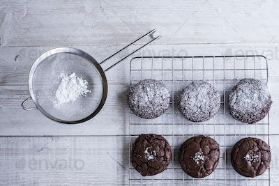 A tray of cooling chocolate brownies, and a sieve with icing sugar for decoration.