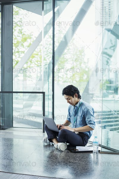 Businessman wearing blue shirt sitting on floor indoors, leaning against glass wall, working on