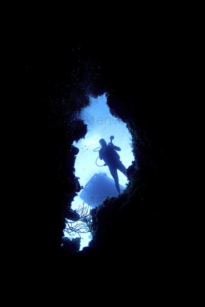 View through a tunnel on Bloody Bay Wall, Little Cayman.  Looking upward at silhouette of diver and