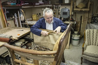 Caucaisan senior male upholsterer working on a chair in his garage shop.