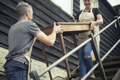 Two people, a man and a young woman carrying an antique wooden table up steps.
