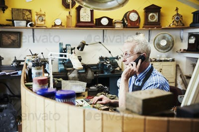 A clock maker on the phone in his workshop.