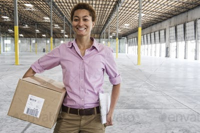 Black female holding cardboard box and standing in front of loading dock doors in a new empty
