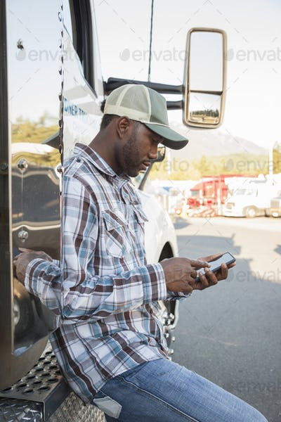 Black man truck driver texting while standing next to his truck cab parked in a lot at a truck stop.