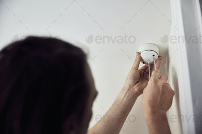 An electrician screwing the cap on a light fitting on the ceiling.