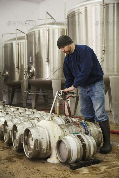 Man filling metal beer kegs with foaming beer from the fermentation chambers in a brewery.
