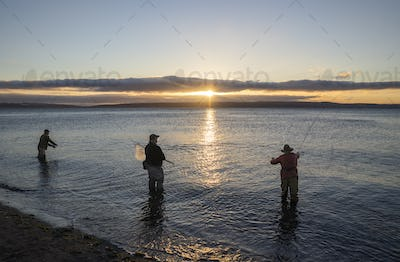 Two fly fishermen cast for searun coastal cutthroat trout and salmon at sunrise with their guide