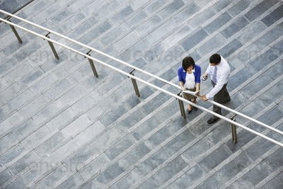 View from above looking down on a businesswoman and businessman standing on steps up to a large