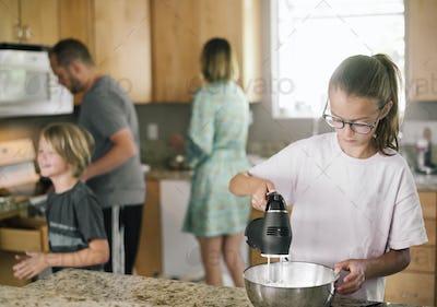 Family preparing breakfast in a kitchen.