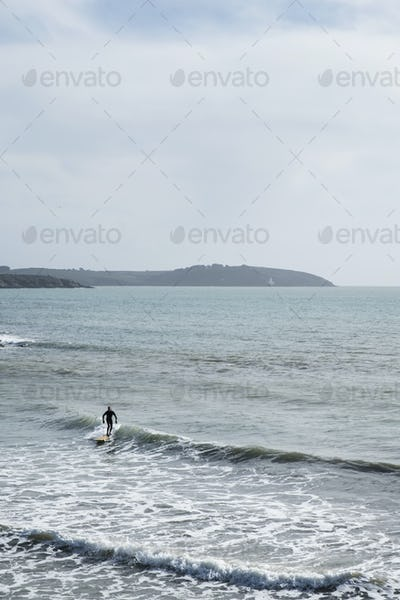 Surfer wearing wet suit riding ocean wave close to shore. need model release form!
