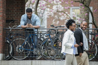 A bicycle rack with locked bicycles, a man texting and a couple walking by.