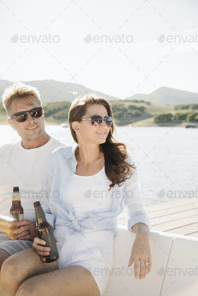 Man and woman on a sail boat, having a drink.