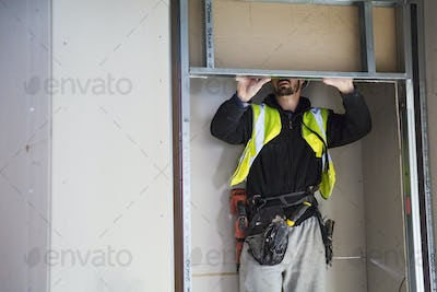 A carpenter in a small space fitting a shelf into a wall cupboard.