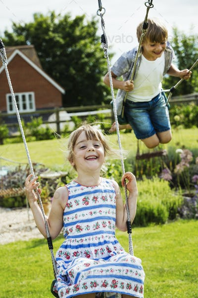 Smiling boy wearing shirt and denim shorts and girl in a sundress on swings in a garden.