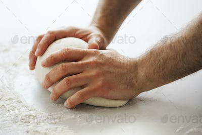 Close up of a baker kneading and shaping a portion of bread dough into a ball.
