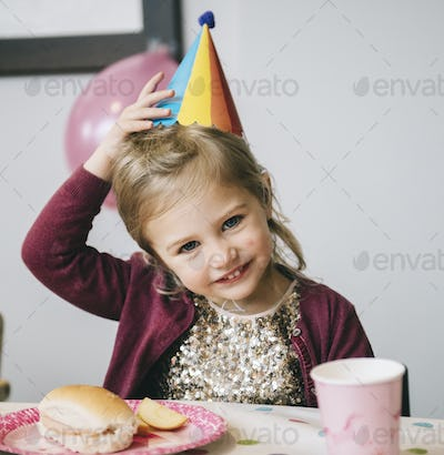 A young girl in a party hat at a birthday party.