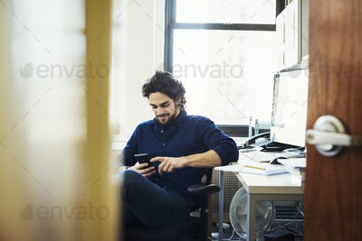 A man sitting on his own in an office checking his phone, seen through an open door.