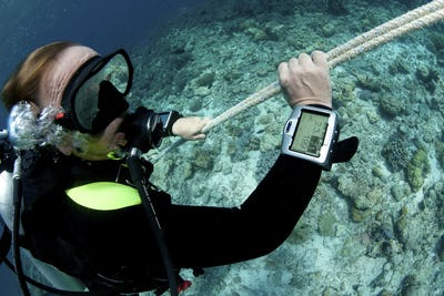 Scuba diver monitors his dive computer screen with information on time and depth while ascending