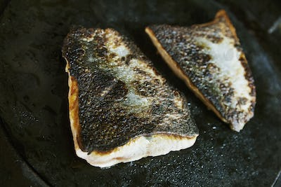 Close up of a pan-fried fillet of fish with crispy skin.