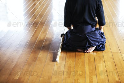 Rear view of Japanese Kendo fighters kneeling on wooden floor.