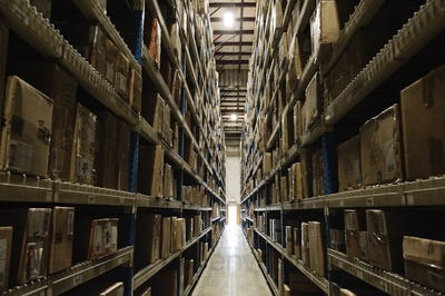 View down an aisle of racks holding cardboard boxes of product on pallets  in a large distribution