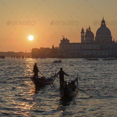 Two gondoliers on the Canale Grande in Venice, Italy, at sunrise, with the dome of Santa Maria della