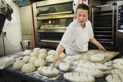 Woman standing at a table, placing freshly baked loaves of bread on a wooden board.