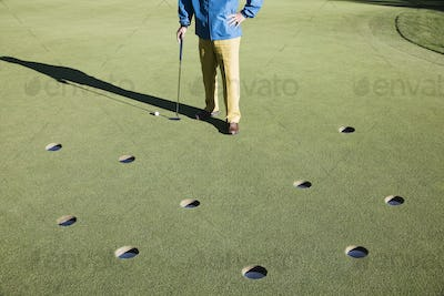 A golfer with way too many choices in possible putts on the greeen of a golf course.