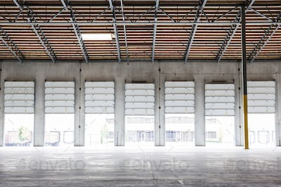 Wide angle interior view of largeempty warehouse and loading dock doors