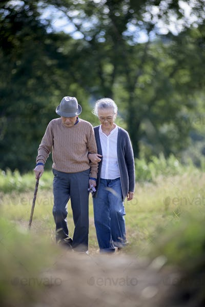 Husband and wife, elderly man wearing hat and using walking stick and elderly woman walking along
