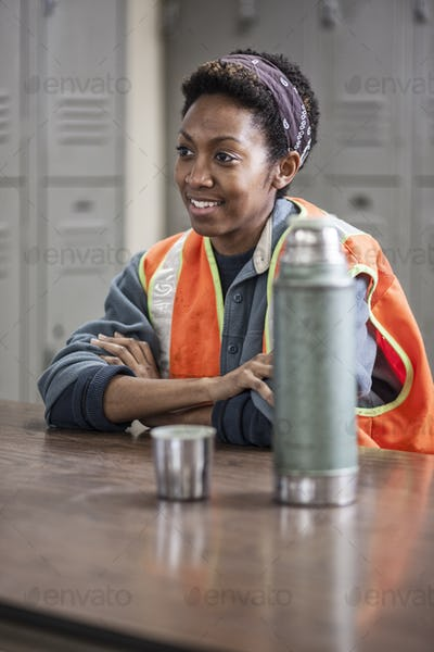 Black woman factory worker wearing a safety vest and  taking a break in a factory break room.