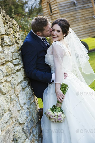 A bride and groom on their wedding day, laughing and embracing.