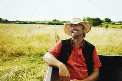 A man in a straw hat sitting in the back of a pick up truck.