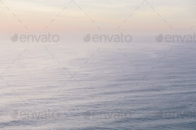 The open ocean, water surface calm and grey and the glow of the sun at dawn on the horizon.