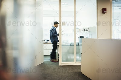 A man standing in an office looking down at pieces of paper.