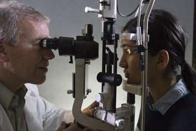 Caucasian man opthamologist using a slit lamp tanometer on a patient's eye.