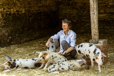 Smiling senior woman sitting in barn with Gloucester Old Spot pigs.