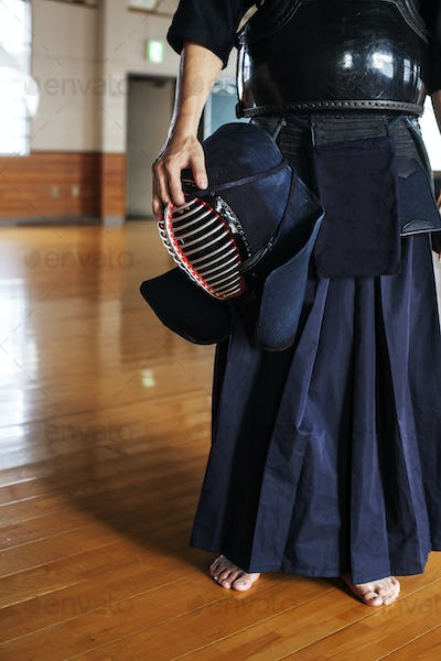 Male Japanese Kendo fighter standing in a gym, holding Kendo mask.