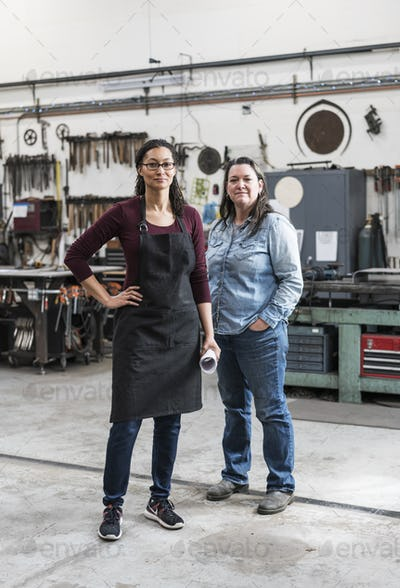 Two women wearing apron and Denim shirt standing in metal workshop, smiling at camera.