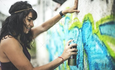 A young woman spray painting graffiti onto a wall.