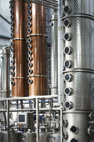 Tall copper distillery chambers in a brewery, brewing storage tanks in copper and steel.