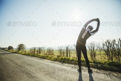 A man preparing for a cycle ride, with raised arms stretching and leaning sideways. A country road.