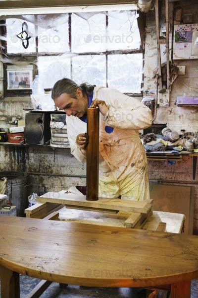 Man standing in a carpentry workshop, wearing protective suit and gloves, applying varnish onto a