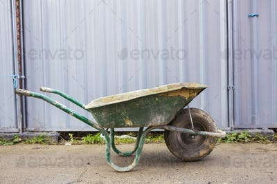 Green wheelbarrow on a building site in front of a metal container.