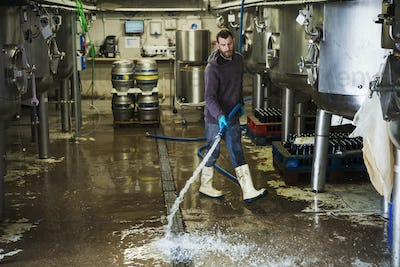 Man working in a brewery, cleaning floor with water hose.