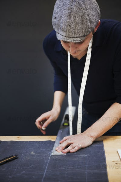 A man measuring up and marking with tailor's chalk, a piece of grey fabric using a metal ruler.