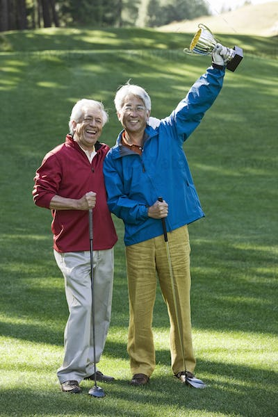 Two senior male golfing buddies with a trophy they just won playing golf.